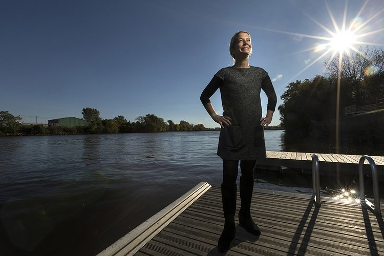 Woman stands on a dock in front of river