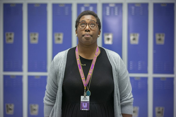 Woman looks up while standing in front of purple lockers