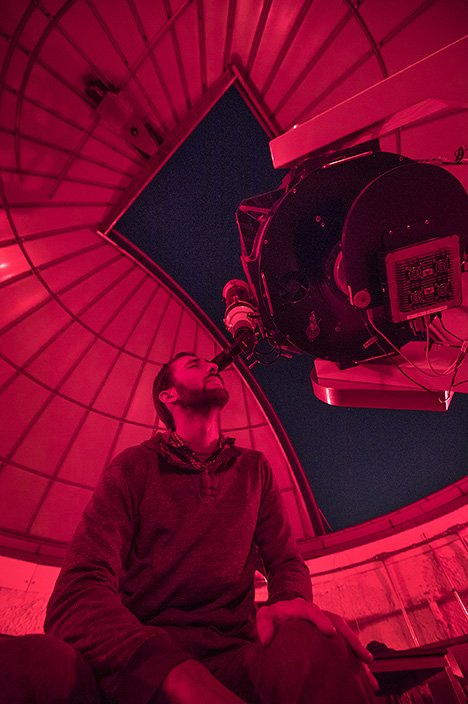 Male student looks through telescope at the night sky