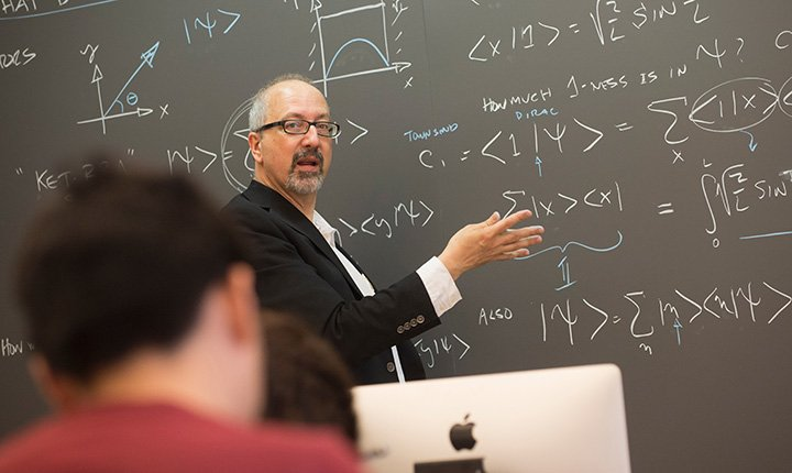 Mike Brown teaches in front of blackboard