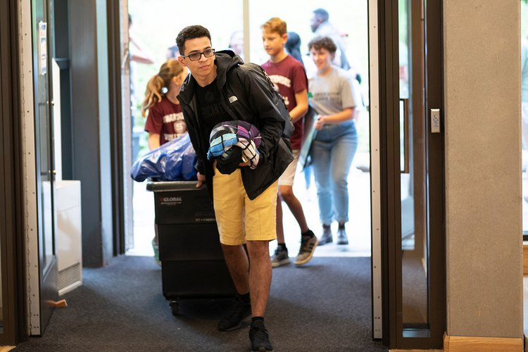 Student pushes cart with belongings into dorm