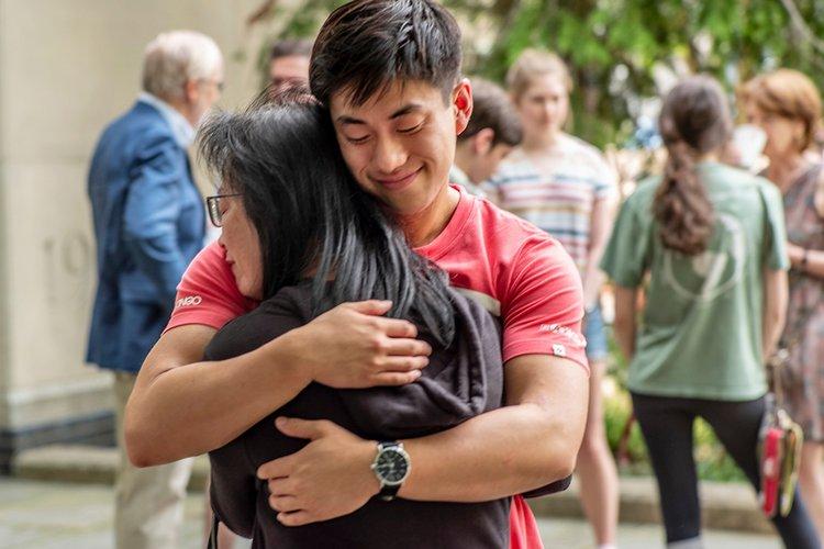 Student hugs family member