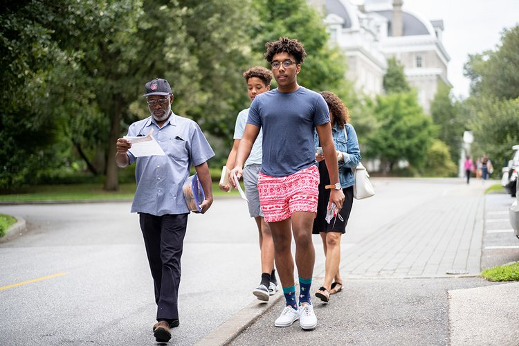 Student walks with Parrish in background