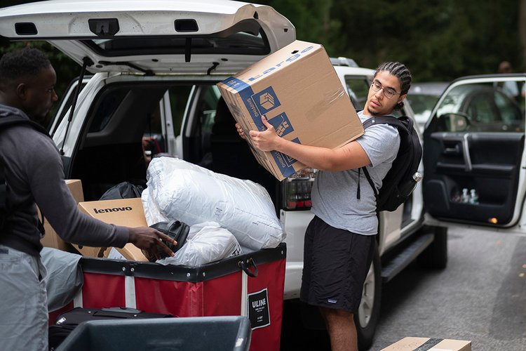 Student moves box from car