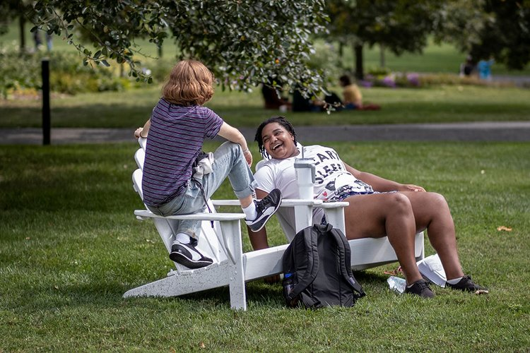 Two students sit outside in white adirondack chairs