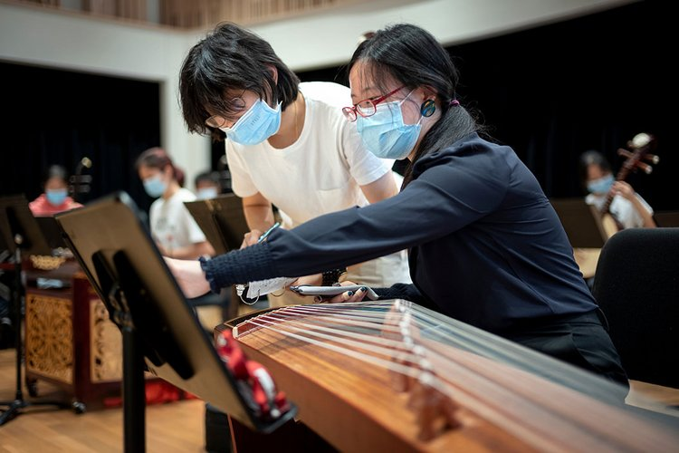 Students wearing masks play instrument