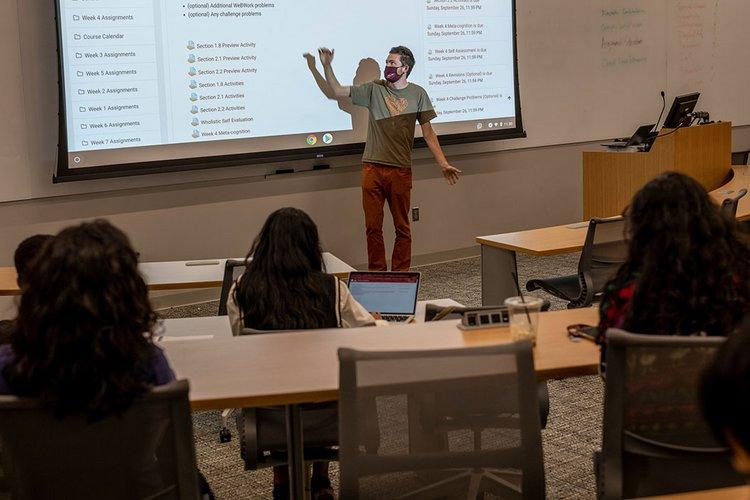 Professor wearing masks gestures at projector screen