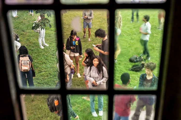 Students on lawn framed by glass window pane