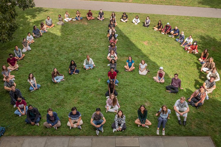 Students sitting on lawn form giant peace sign