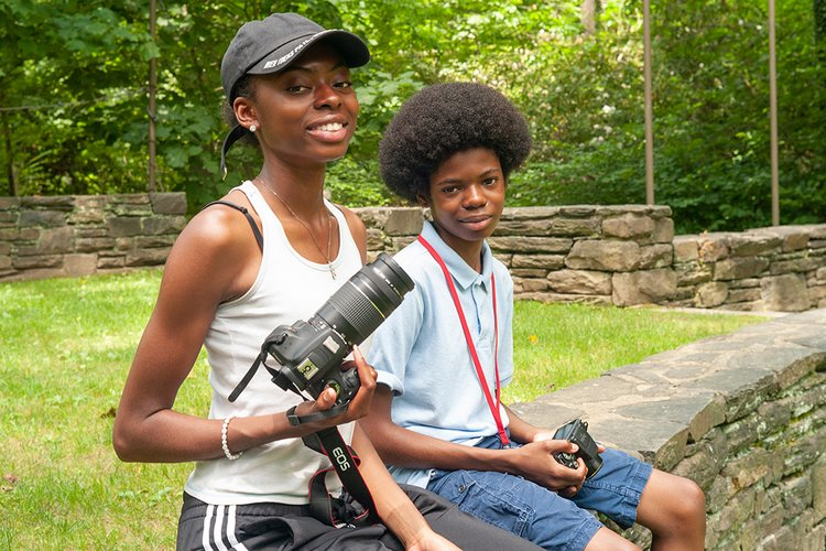 Two students sit outside with digital cameras