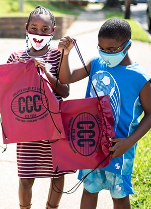 Two children wearing masks hold red drawstring bags on sidewalk.