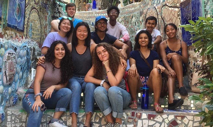 The Chester Fellows sit together on steps at Philadelphia's Magic Garden