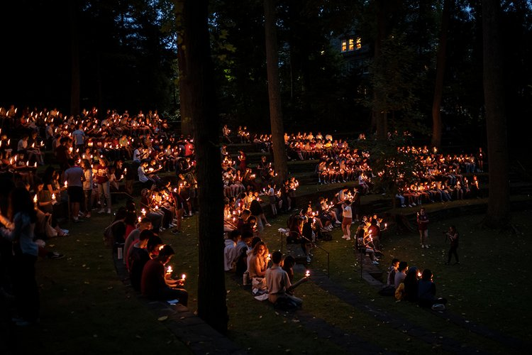 Students congregate outdoors with lit candles