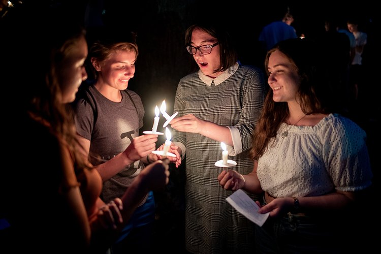 Students hold candles at first collection