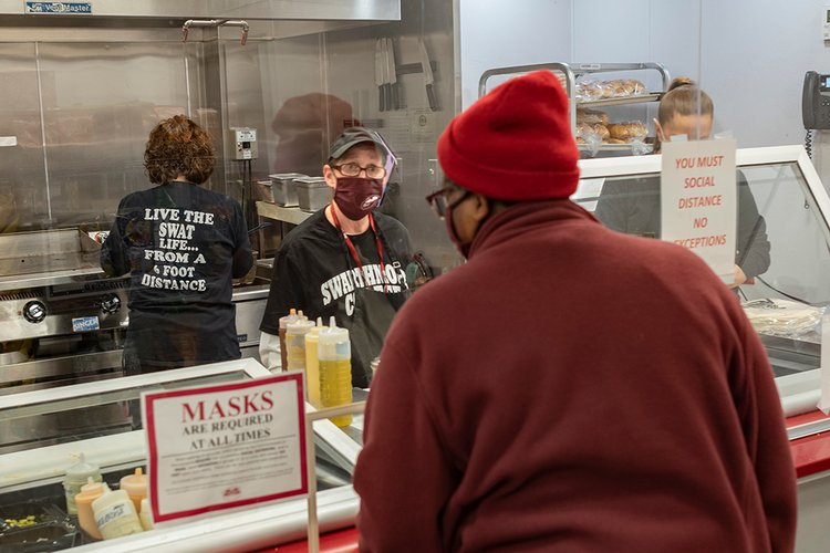 Person wearing mask stands behind plexiglass and takes order from customer at grill