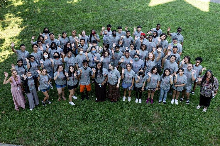 Students wearing gray wave at camera