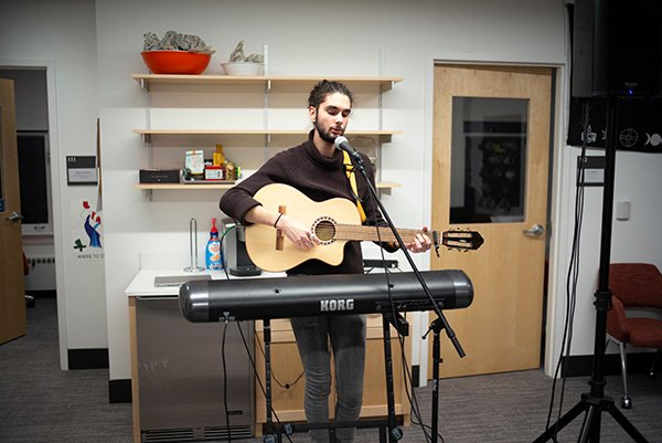 Student plays guitar at IC dedication event