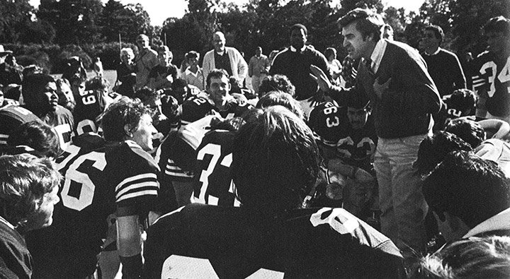 Coach Tom Lapinski huddles with the football team