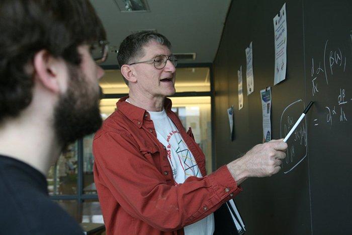 Professor teaches math at chalkboard