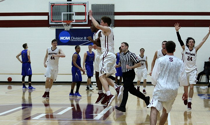 Men's basketball team celebrates win.