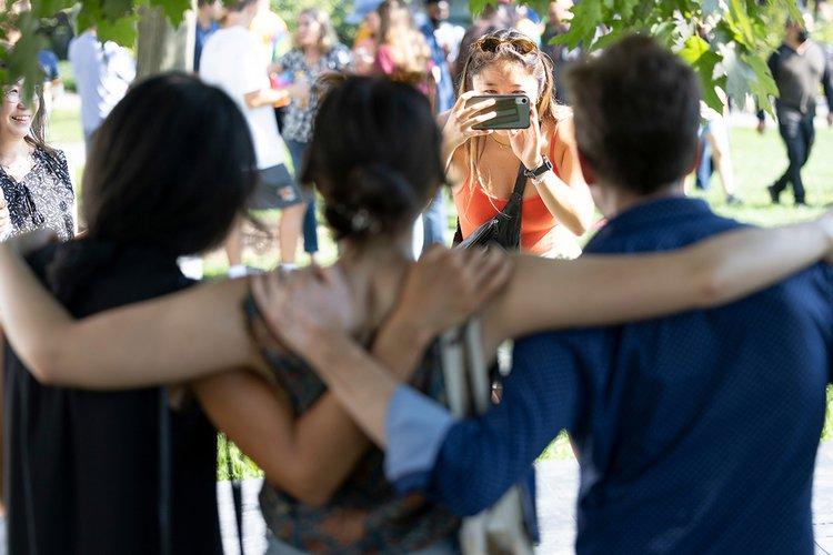 Students hug while wearing masks