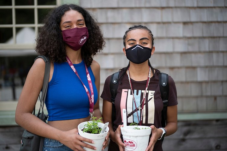 Students smile while holding potted plants