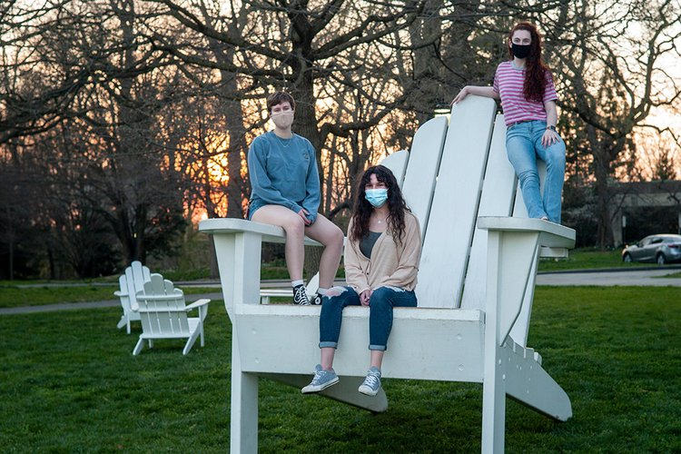 Three students wearing masks sit on oversized white Adirondack chair during sunset