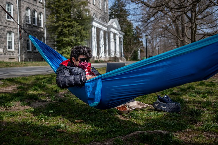 Student wearing mask and sunglasses uses laptop in blue hammock.