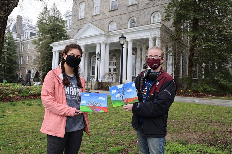 Two students wearing masks hold up paintings of bare trees.