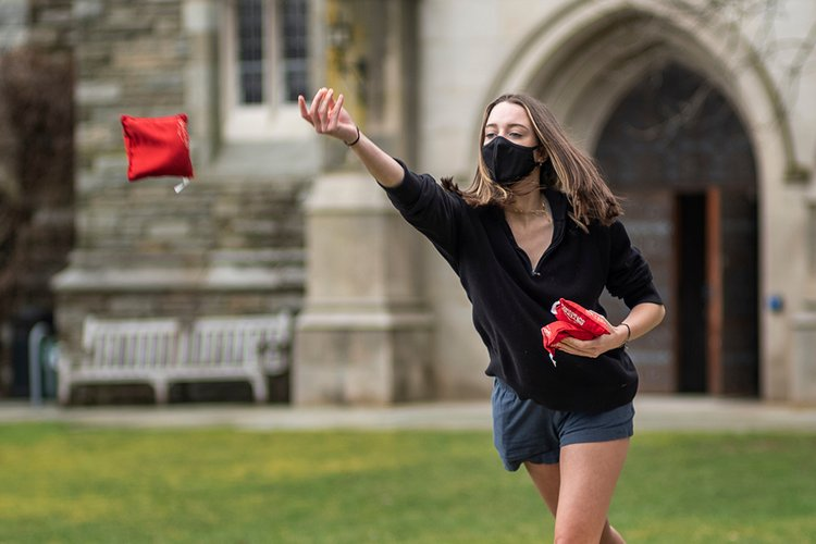 Student wearing mask tosses red bean bag outdoors.