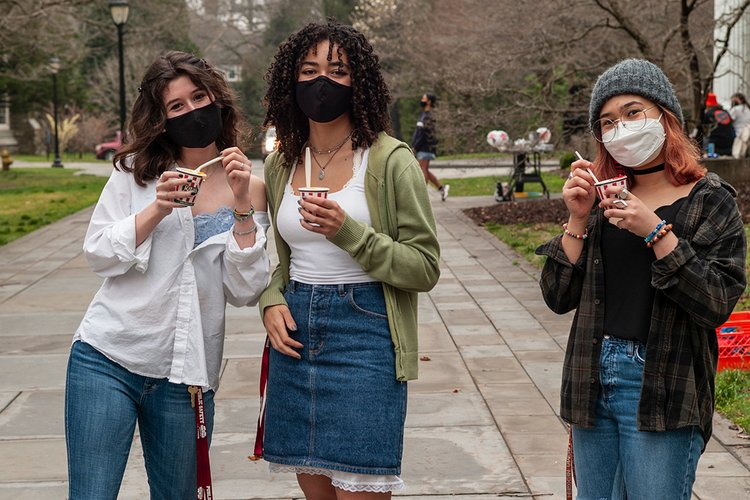 Students wearing masks eat water ice from Rita's outdoors.