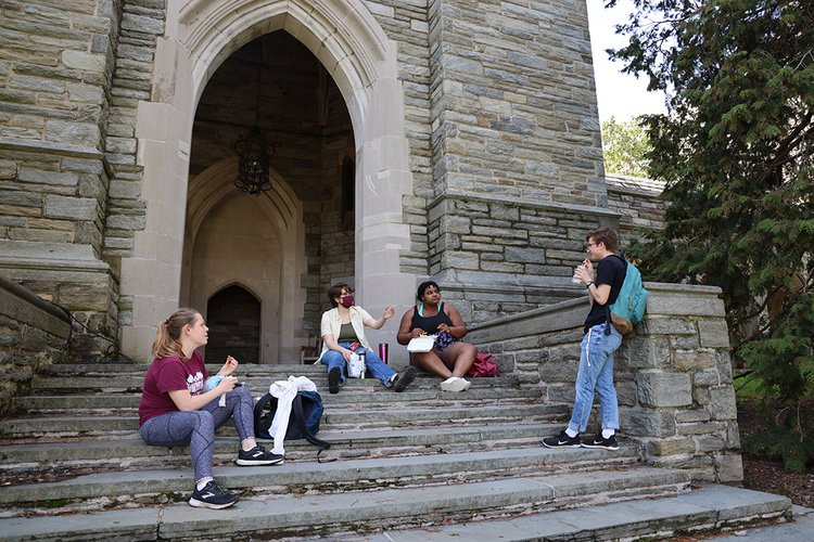 Students sit on steps of bell tower and eat lunch