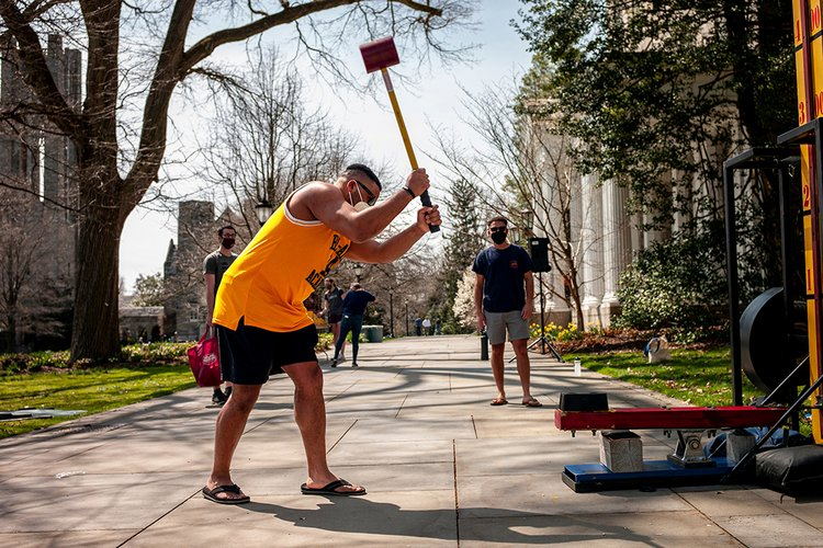 Student in yellow tank top plays carnival game with hammer