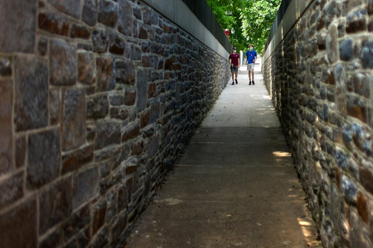 Two students in distance walking down path lined by brick wall on both sides