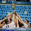 Swimmers hold their championship trophy above theirs heads in the pool