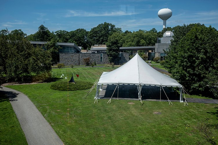 Large white tent outdoors in science quad surrounded by trees