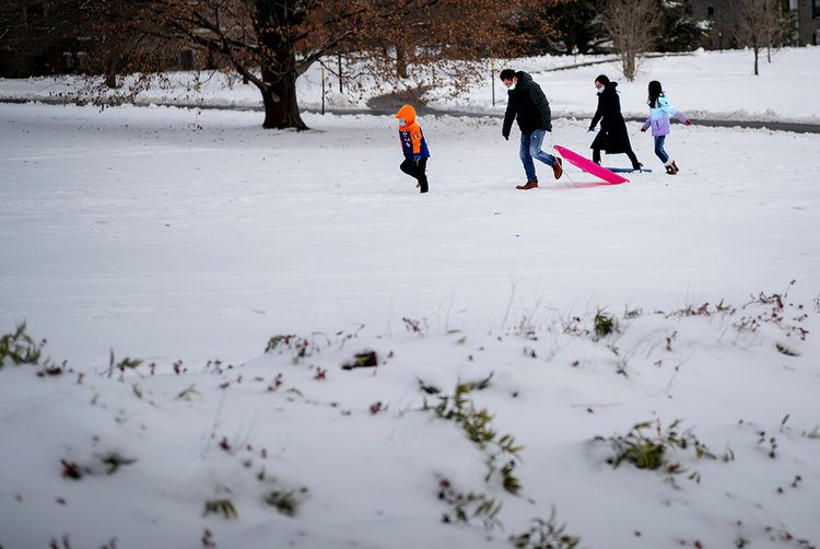 Family in snow holding sled