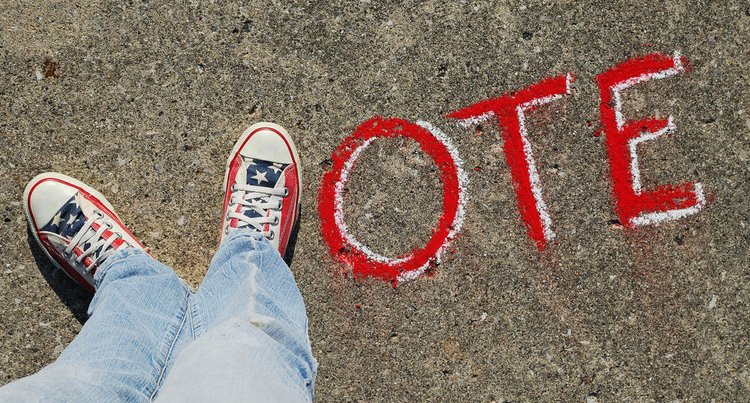 "A photo of the word ""vote"" form by two sneakered feet forming a letter V followed by chauking of ""ote"""