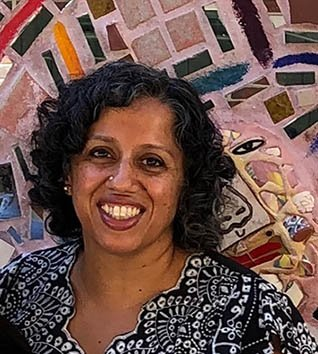 Bakirathi Mani in front of a colorful mosaic