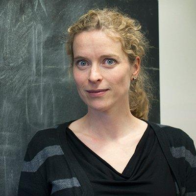 Eva-Maria Collins in front of a blackboard