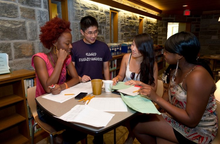 Group of students gathered around a table, smiling and studying