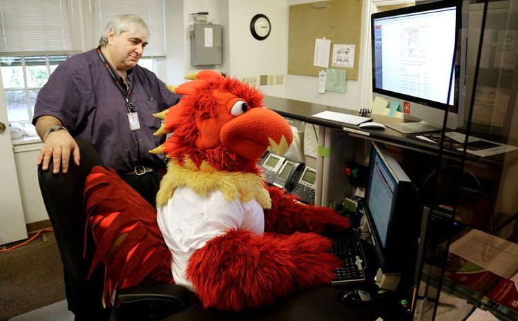 Swarthmore Mascot Phineas Phoenix sits at the computer.