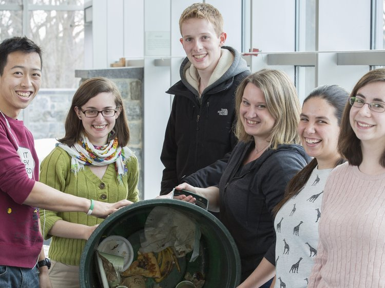 Staff and students of the Office of Sustainability pose with compost bins