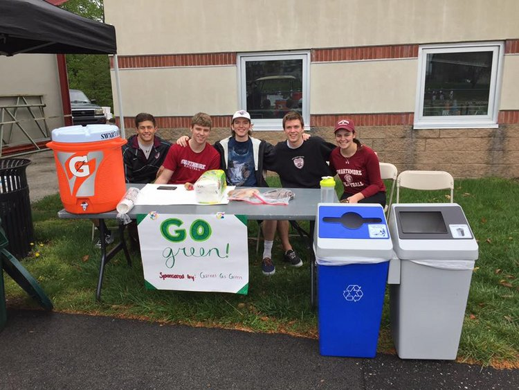 """Swarthmore student athletes manning a table that is providing drinking water with compostable cups. A recycling bin next to a waste bin can be seen on the right, and a poster with the words """"Go Green"""" is taped to the table."""