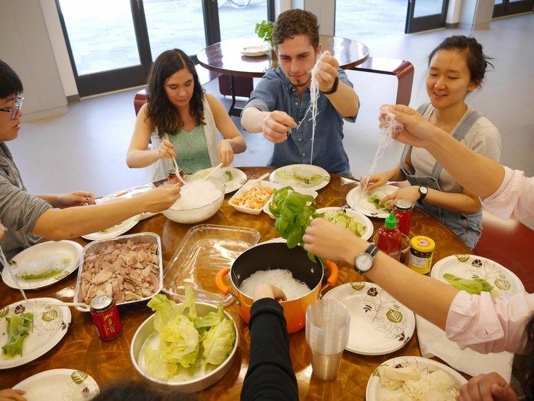 A group of students enjoying what appears to be a meal consisting of Vietnamese vermicelli noodles and some leafy greens