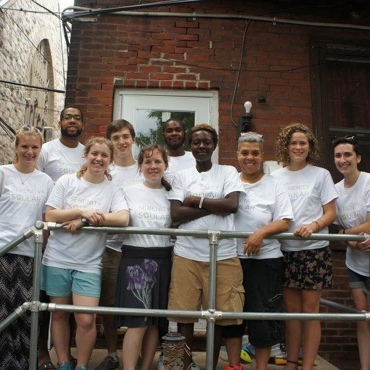 A group of students and Serenity House members, all wearing white T-shirts with the Serenity Soular logo,  pose for a picture on a balcony.