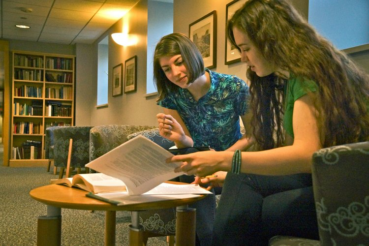 A WAM discusses a paper with a student in the Trotter hallway