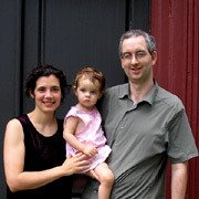 Assistant Professor of Philosophy Alan Baker standing with his wife and child