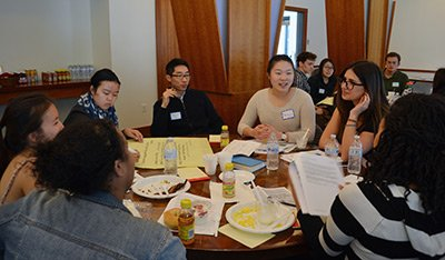 Student leaders talk to each other around a table