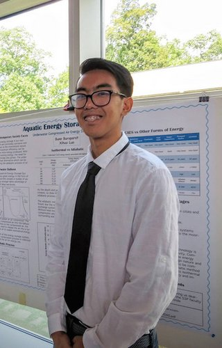 Bunn Buraparat '20 standing in front of his S3P poster